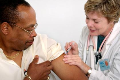 Nurse administering a vaccination to a patient in his left upper arm