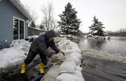 Person stacking sandbags in preparation for flooding