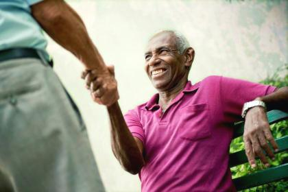 An elderly man seated on a bench shakes hands with a man standing up.